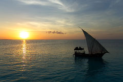 Stunning sunset captured north on Zanzibar, Tanzania, Africa. Sailboat passing by stock photos