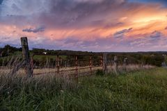 Stunning Sunset from Farm - Kentucky. A beautiful pink and blue hued sunset on a partly cloudy evening, viewed through a worn farm gate in central Kentucky Stock Images