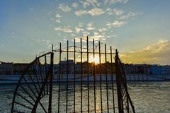 Stunning sunset on Guadalquivir River, Sevilla. A magic moment on Guadalquivir River in Sevilla, sunlight passes through a small gate and colors the sky in many royalty free stock image