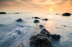 Stunning sunset moment seascape,soft wave hitting the rock over cloudy sky Stock Photos