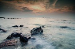 Stunning sunset moment seascape,soft wave hitting the rock over cloudy sky Stock Images