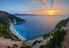 Stunning sunset over Myrtos Beach in Kefalonia. Stunning sunset over Myrtos Beach with magical sun rays, Kefalonia island, Greece Stock Photos