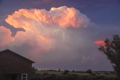 Stunning Thunderstorm and Lightning at Sunset. A Stunning Cumulonimbus cloud at sunset. With brilliant colors and a lightning streak during a midwest stock images