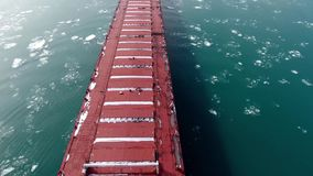 Stunning top 4k aerial drone panorama shot of huge tanker container freight cargo ship vessel sailing slow in ice river stock footage