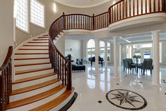 Stunning two story entry foyer with marble mosaic tiled floor. Stunning spacious two story entry foyer boasts marble mosaic tiled floor and grand staircase with stock photography
