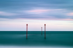 Stunning vibrant conceptual image of posts in sea standing senti Royalty Free Stock Photography
