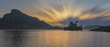 Stunning vibrant landscape image of mountain and lake during colorful sunset long exposure. Beautiful landscape image of mountain and lake during colorful sunset royalty free stock images