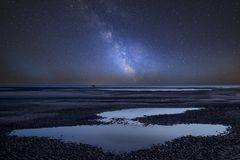 Vibrant Milky Way composite image over landscape of beach at low. Stunning vibrant Milky Way composite image over landscape of beach at low tide Royalty Free Stock Images