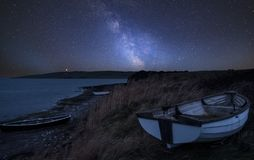 Vibrant Milky Way composite image over landscape of Old abandone. Stunning vibrant Milky Way composite image over landscape of Old abandoned rowing boats on Royalty Free Stock Images