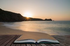Stunning vibrant sunrise landscape image of Porthcurno beach on South Cornwall coast in England coming out of pages in magical. Beautiful colorful sunrise royalty free stock photo