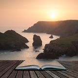 Stunning vibrant sunset landscape image of Kynance Cove on South Cornwall coast of England coming out of pages of open story book. Beautiful colorful sunset stock photo