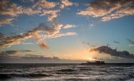 Stunning vibrant Winter sunset over long exposure receding waves Stock Image