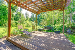 Stunning view from backyard farm pergola. Open farm house pergola with rustic bench, chair and flower pots Stock Photo