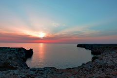 Stunning view during the sunset at rocky cliff in the ocean on menorca. Stunning view during bloody red sunset at rocky cliff in the ocean on menorca stock images