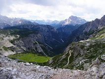 Stunning View of the Deep Valley in Sexten Dolomites Mountains and on distant Mountains. Stunning View into the Deep Valley in Dolomits Mountains Royalty Free Stock Photos