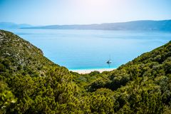 Stunning view of Fteri beach with white sailboat in hidden bay, Kefalonia, Greece. Surrounded by mediterranean royalty free stock photo