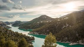 Stunning view of the lake El Portillo with the sun shinning above the mountains. Fantasy land. The sun is about to set behind the mountains in this landscape stock images