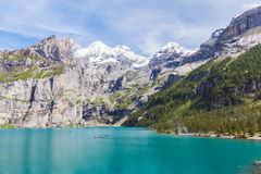 Stunning view of Oeschinensee (Oeschinen lake) with Bluemlisalp. And Frundenhorn of swiss alps on Bernese Oberland. Photo taken in summer on the hiking path at Stock Images