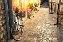 Stunning view of stoned paved street in old town on sunrise. Pots with flowers standing on vintage bicycles along a wall. Sun light on stone walls. Travel Royalty Free Stock Photos