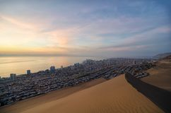 Stunning view to sand dunes, ocean and Iquique city at sunset Royalty Free Stock Photo