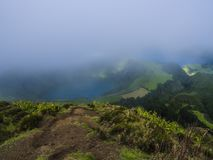 Stunning view on volcanic lakes. Green Lagoa de Santiago and blue Lagoa Azul with Sete Cidades village, partially. Covered by fog mist and clouds. Sao Miguel in stock photo
