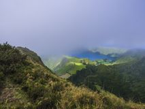 Stunning view on volcanic lakes. Green Lagoa de Santiago and blue Lagoa Azul with Sete Cidades village, partially. Covered by fog mist and clouds. Sao Miguel in stock photography