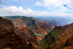 Stunning view of Waimea Canyon Kauai Hawaii. Stunning panoramic view of the red and green of Waimea Canyon State Park in Kauai Hawaii with a waterfall in the royalty free stock images