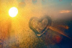 Stunning vintage amber sunrise light with heart love inscription on frozen window glass. Soft focus. Background with copy space