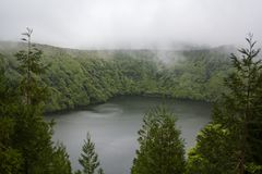 Stunning volcanic Lagoon surrounded by forest and fog stock photos