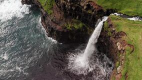 Stunning waterfall splashing from cliff aerial view. Mulafossur waterfall near Gasadalur Village at Faroe Islands