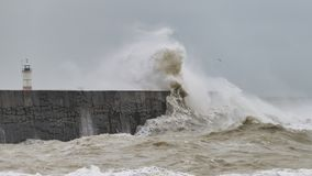Stunning dangerous high waves crashing over harbor wall during windy Winter storm at Newhaven on English coast. Stunning waves crashing over harbor wall during royalty free stock images