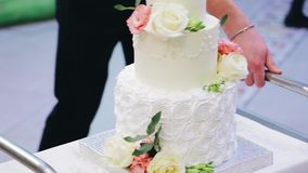 A stunning wedding cake is brought on a cart. Holiday. Nice shots.