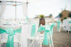 Stunning blue trim decorates the back of these white folding cha. Stunning wedding stock photography from Zakynthos Greece! A stunning summer wedding reception Royalty Free Stock Photo