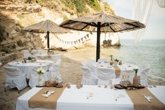Small tables under parasols await the lucky guests of this intim. Stunning wedding stock photography from Zakynthos Greece! A stunning summer wedding reception Stock Photo