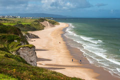 Stunning Whiterocks Beach seen from above, Portrush, Northern Ireland. People walking on a long sandy beach backed by sand dunes and limestone cliffs Royalty Free Stock Image