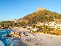 Stunning wide angle aerial drone evening view of Lion`s Head Mountain in Cape Town. South Africa, seen from Camps Bay Beach. White sand and stunning villas Stock Photos