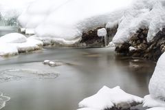 Stunning winter landscape, stones on wintry river covered snow Royalty Free Stock Photo
