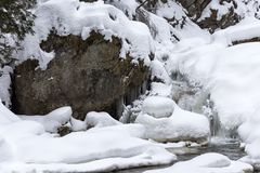 Stunning winter landscape, stones on wintry river covered snow a Stock Image