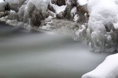 Stunning winter landscape, stones on wintry river covered snow Royalty Free Stock Photos