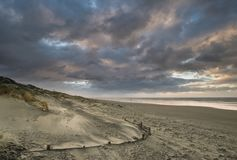 Stunning Winter sunrise over West Wittering beach in Sussex England with wind blowing sand across the beach stock photography