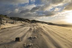 Stunning Winter sunrise over West Wittering beach in Sussex England with wind blowing sand across the beach. Beautiful Winter sunrise over West Wittering beach stock photography