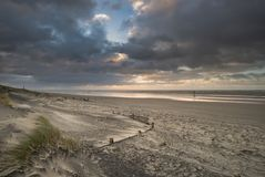 Stunning Winter sunrise over West Wittering beach in Sussex England with wind blowing sand across the beach. Beautiful Winter sunrise over West Wittering beach royalty free stock photos