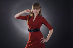 Stunning woman in red dress on black background Stock Photography
