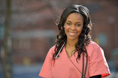 Stunning young African American female student on campus. Stunning young African-American female healthcare professional in Pink scrubs shown outside with a Royalty Free Stock Images