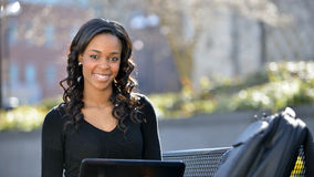 Stunning young African American female student on campus. Stunning young African American female student sitting on a bench in the shade using a laptop computer Stock Photography