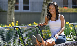 Stunning young African American woman - white tank. Portrait of a stunning young African-American woman in white tank top outdoors in late afternoon sun - seated royalty free stock photo