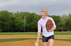 Stunning young blonde female softball player. In pink and white baseball jersey shirt - pitching Stock Image