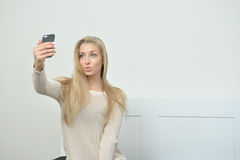 Stunning young blonde model takes a selfie Royalty Free Stock Photography