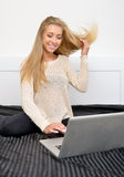 Stunning young blonde model uses laptop. Stunning young blonde woman flips her hair as she sits on bed using her laptop computer Stock Photo
