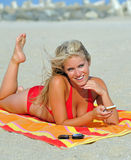 Stunning young blonde woman on beach in bikini Stock Image